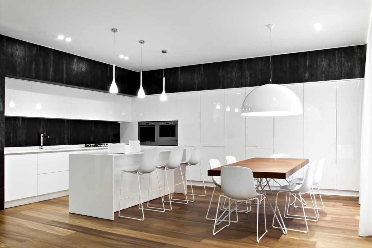 The kitchen has well-defined volumes and containers that incorporate all the structural elements, in a palette of white and black color that blends with the shades of the wood. The wall system in glossy lacquered MDF with metal doors and compartments for champagne-colored enameled metal, rests on a natural stone cladding in Trani.