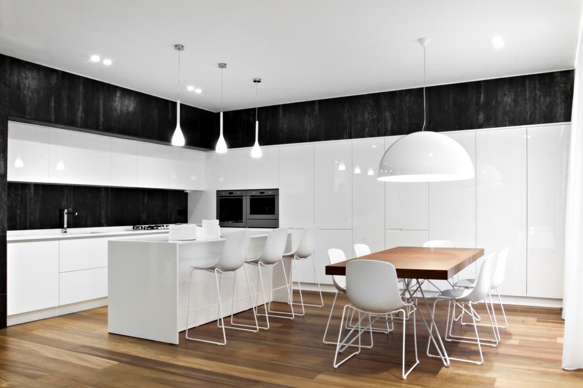 キッチンには、木の色合いとのブレンド白と黒の色のパレットで、すべての構成要素を組み込んで明確に定義されたボリュームおよびコンテナを持っています。 シャンパン色のホーロー用の金属製のドアや区画を有する光沢のある漆塗りのMDFの壁システムは、トラーニの天然石のクラッド上に載っています。