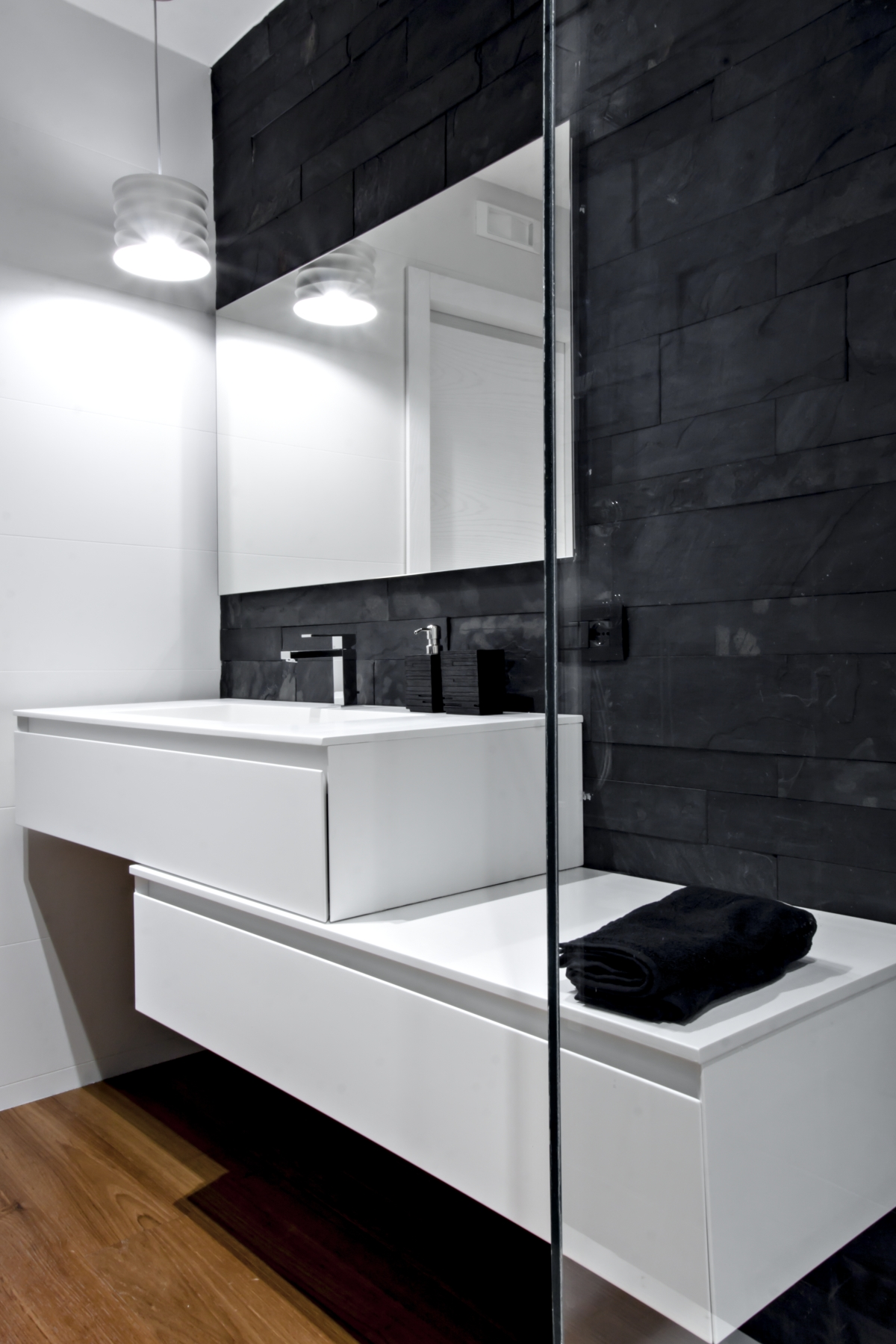 Bathroom wall covered with black slate and essence furniture and stone. Parquet Burmese Teak.